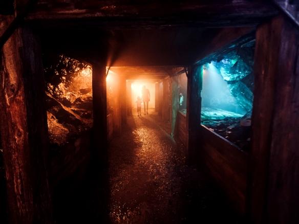 Deux personnes qui marchent dans une mine sombre abandonnée.