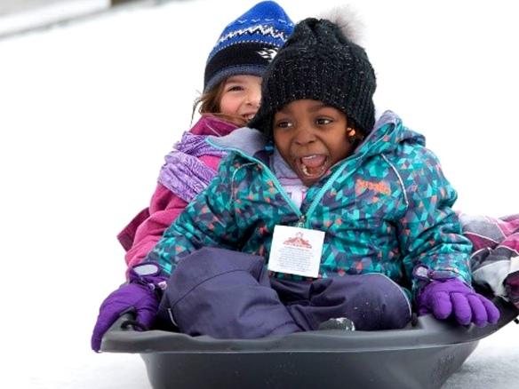 Deux petites filles qui descendent une pente enneigée en traîneau.
