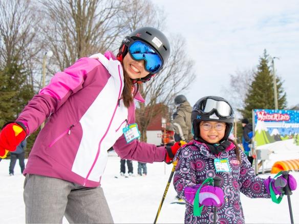 Un adulte qui enseigne à skier à un jeune enfant.